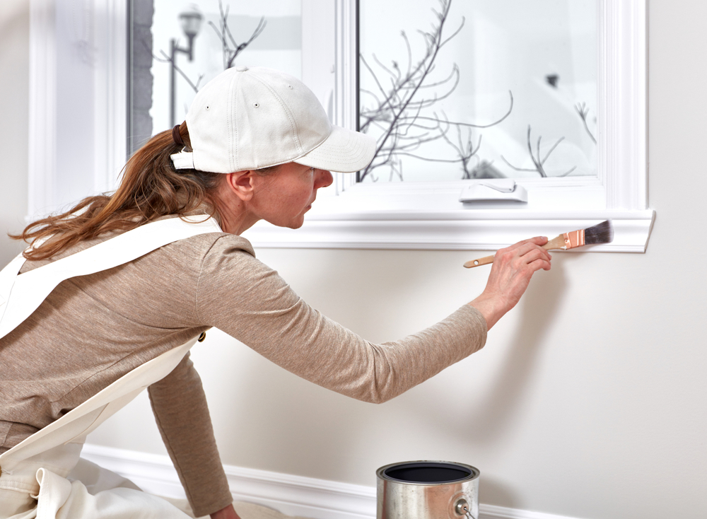 A woman paints window trim with semi-gloss paint for a nice contrast