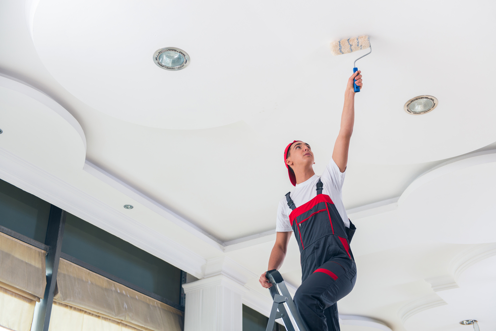 A painter paints the ceiling with a flat paint that won't show any imperfections in the wall.