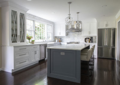 Remodeled kitchen with white cabinets and island with seating