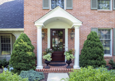Front door and archway of a house with a brick facade