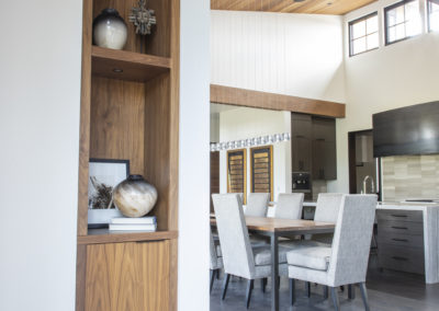 Open wooden shelves between kitchen and dining area
