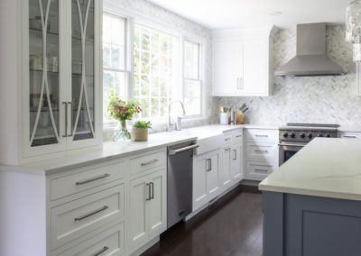 Remodeled white kitchen cabinets and blue and white island