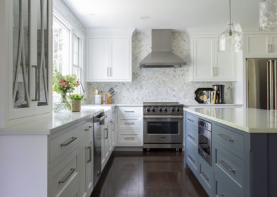 Renovated kitchen with white cabinets, blue and white island, and hardwood floor