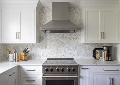 New range hood, oven, and white cabinets
