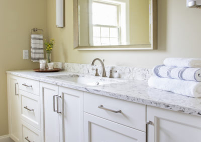 Remodeled bathroom sink with white cabinets and a large mirror