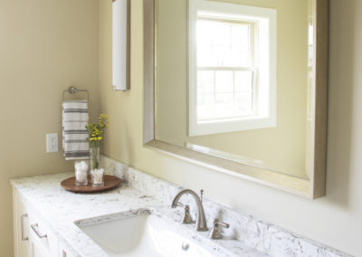 Remodeled bathroom sink with a large mirror