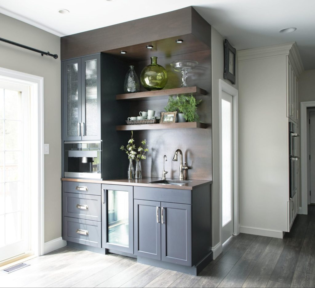 A small bar area added to the side of a kitchen adds space and functionality.