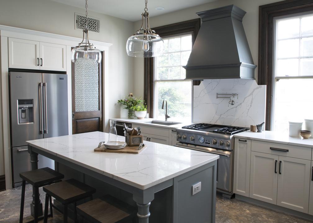 A kitchen with a custom range hood and spacious island.