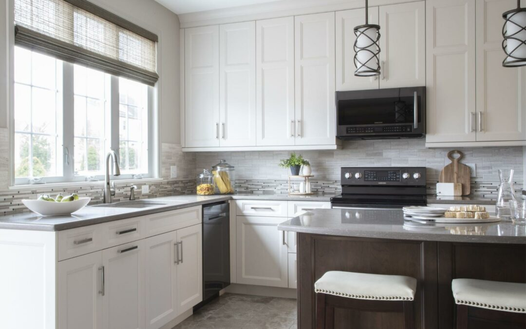 A kitchen with white Shaker style cabinets and a contrasting island.