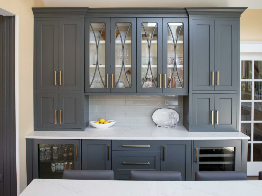 A wall of kitchen cabinets, some with glass fronts to display dishes within.